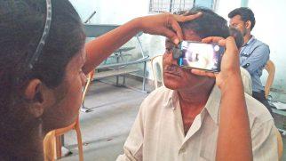 Augen-Screening mit umgerüsteten Smartphones in Indien: Geschulte Pflegekraft nutzt ein Smartphone als direkten Augenspiegel; © privat