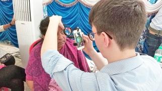 Augen-Screening mit umgerüsteten Smartphones in Indien: Dr. Maximilian Wintergerst untersucht das Auge einer Patientin mit einer indirekten Smartphone-Lösung; © privat