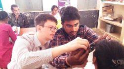 Augen-Screening mit umgerüsteten Smartphones in Indien: Dr. Maximilian Wintergerst (li) zeigt wie ein umgerüstetes Smartphone als Augenspiegel funktioniert; © privat