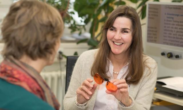 Daniele Brohlburg, eine dunkelhaarige Frau, lächelt eine andere Frau an und hält eine spezielle Hilfsbrille in der Hand.